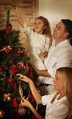 Young Family Decorating The Christmas Tree