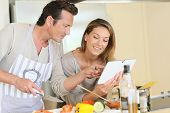 picture of 35 to 40 year olds  - Couple in kitchen looking at pasta dish recipe on tablet - JPG