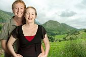 Portrait of a happy couple against a green landscape