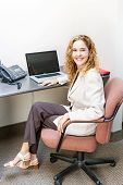 picture of workstation  - Happy businesswoman sitting at workstation in office with computer - JPG