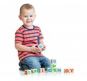 Kid playing with letter blocks isolated