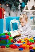 Cute boy sitting at Christmas tree with a book