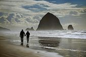 image of cannon  - Looking at Haystack Rock Cannon Beach Oregon a couple is strolling along the shoreline - JPG