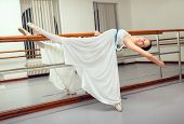 Beautiful classic ballet dancer in white tutu posing on one leg next to handle bar.