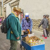 LA PAZ, BOLIVIA, MAY 8, 2014: Senior tourist buys nuts from street seller