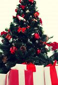 holidays, winter and celebration concept - close up of christmas tree and presents
