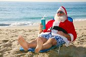 foto of christmas claus  - Santa Claus relaxes lying on the beach on some tropical island in the sun - JPG
