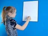 the girl draws on a white plastic board