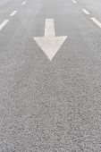 White Painted Arrow On Grey Asphalt Road