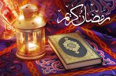 image of quran  - A beautiful image of Ramadan lantern beside Quran with little golden rays - JPG