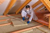 stock photo of thermal  - Man laying thermal insulation layer under the roof  - JPG