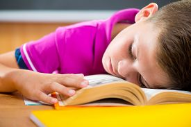 stock photo of schoolboys  - Tired schoolboy sleeping on book in classroom - JPG