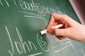 stock photo of grammar  - Teacher hand writing grammar sentences on blackboard background - JPG