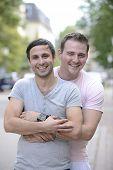pic of gay couple  - Happy gay couple outdoors hugging and smiling - JPG