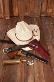 stock photo of pistols  - A cowboy hat and black powder pistol on a wooden background - JPG