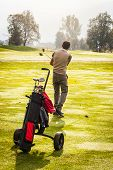 stock photo of caddy  - a golf player playing on a beautiful golf course and a golf bag full of golf clubs - JPG