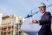 stock photo of blueprints  - Construction manager with blueprints standing in front of construction site - JPG