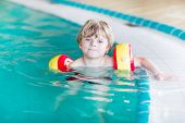 stock photo of floaties  - Active little toddler child cute boy with water wings learning to swim in an indoor pool - JPG