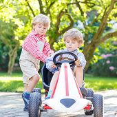 image of pedal  - Two little blond friends boys having fun with pedal car in home - JPG