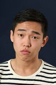 picture of disappointed  - Disappointed young Asian man looking at camera - JPG