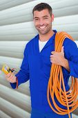 pic of  multimeter  - Smiling electrician with wire roll and multimeter against grey shutters - JPG