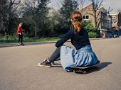 image of skateboard  - A trendy young woman is sitting on a skateboard in a park and is watching other people skateboard in the distance - JPG