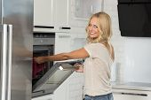 picture of oven  - very pretty young blond woman looking in camera smiling in act of cooking some food with oven in her luxury white modern kitchen - JPG