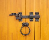 stock photo of hasp  - Wooden door with old forged bolt and lock  - JPG