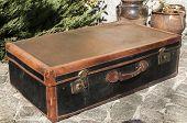 stock photo of paving stone  - Old closed locked retro vintage leather suitcase on stone paved surface closeup - JPG