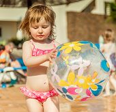 picture of pool ball  - little cute girl playing near the pool with a ball closeup - JPG
