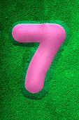 pic of number 7  - The number seven in a pink sponge like texture raised 3D from the green background - JPG