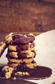 stock photo of chocolate-chip  - Chocolate sauce pouring over a stack of chocolate chip cookies on white curling baking paper against a dark wood background - JPG