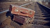 foto of old suitcase  - The image of two old vintage suitcases thrown on railway tracks - JPG
