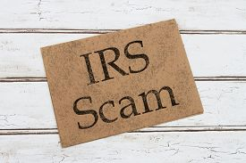 stock photo of irs  - A IRS Scam Warning Card A brown card with words IRS SCAM over a distressed wood background - JPG
