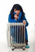 foto of shivering  - Woman shivering and sitting near radiator trying to heat up - JPG