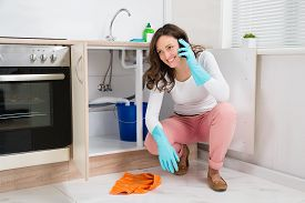 picture of leak  - Happy Woman Wiping Leaking Water While Talking On Mobile Phone - JPG