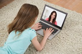 stock photo of chat  - Girl Video Chatting With Woman On Laptop In House - JPG
