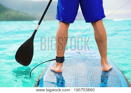 Paddle board man doing standup