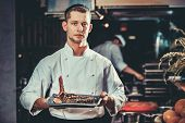 Food concept. Young handsome chef in white uniform hold in his hands ready beef steak meat ribs dish poster