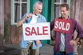 Senior Man Holding Sale Sign While Another Man Holding Sold Sing, House For Sale Concept poster