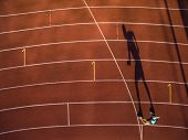 Shot of a young male athlete training on a race track. Sprinter running on athletics tracks. poster