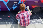 A Young Red-haired Graffiti Artist Paints A New Colorful Graffiti On The Car. Photo Of The Process O poster
