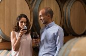 Mature couple tasting a glass of red wine in a traditional cellar surrounded by wooden barrels. Happ poster