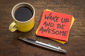 wake up and be awesome - motivational advice on a sticky note with a cup of coffee against rustic wo poster