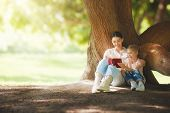 Mother and daughter sitting under the tree on summer lawn. Happy family playing outdoors. Pretty you poster
