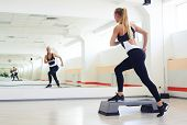 Back view of fitness instructor making step aerobics in gym. Sporty woman training step aerobics in  poster