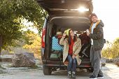Young Couple Packing Camping Equipment Into Car Trunk Outdoors poster