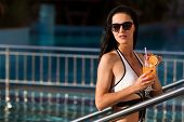 Attractive Young Slim Woman With Long Dark Hair At The Swimming Pool Entrance Holding A Cocktail Wea poster