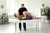 Physiotherapist Working With Patient In Clinic. Rehabilitation Therapy poster