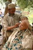 A Uyghur Man getting a shave and haircut at an outdoor barber shop in Kashgar, China